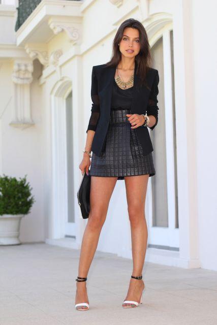 Modelo veste saia cinza escuro, blusa preta , blazer e bolsa no mesmo tom, com sandalia.