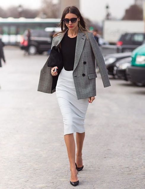 Modelo usa saia midi branca, blazer cinza, blusa e sapato preto.