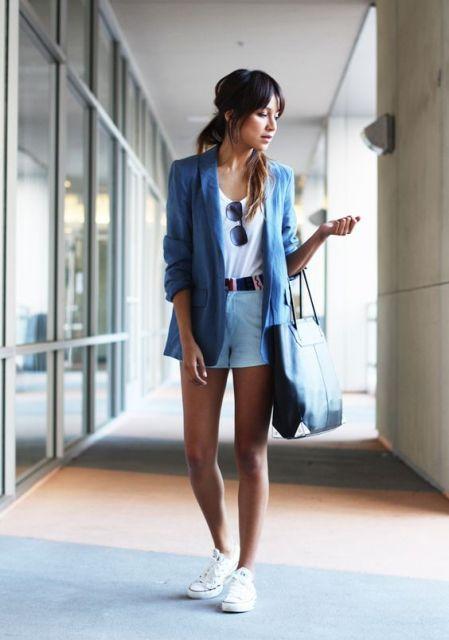 Modelo veste short, azul claro,, blusa branca, blazer azul e tenis branco.