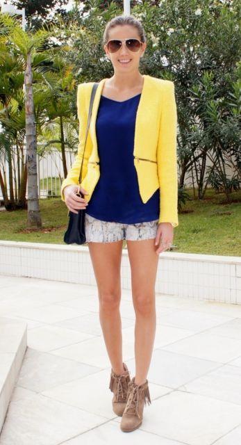 Modelo veste short, blusa azul, sapato com franjas e blazer amarelo.