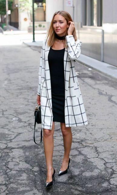 Modelo usa blazer estampado  longo, vestido preto e sapato preto bico fino.
