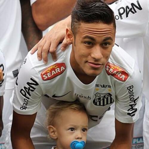 Neymar com cabelo penteado para o lado, posa com seu filho