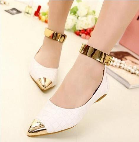 Modelo com pés de sapatilha branca com detalhe dourado na ponta e detalhe no mesmo tom na tira da canela.