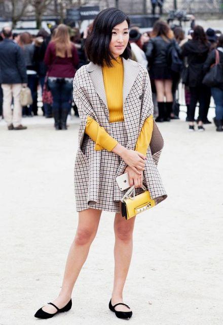 Modelo usa sapatilha preta bico fino, blusa amarela, saia estampada e casaco na mesma estampa na cor preto e branco.