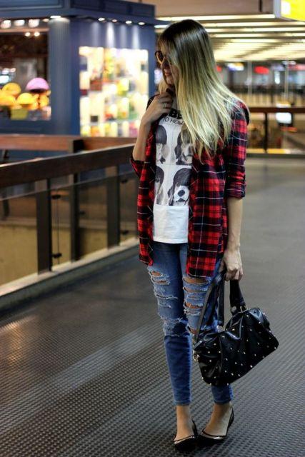 Modelo usa calça jeans azul, sapatilha preta, blusa camiseta branca, casaquinho listrado e bolsa preta de couro.