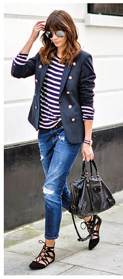 Modelo com calça destroyed, sapatilha de amarraçoes, bolsa de couro preta, blusa listrada e blazer no mesmo tom