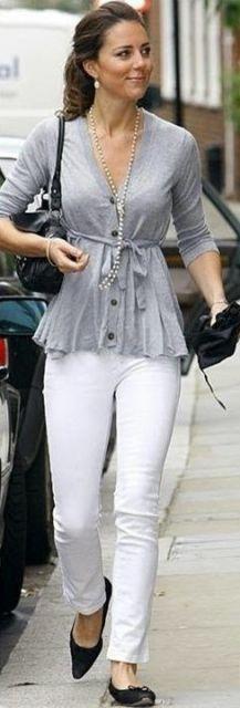 Modelo usa blusa cinza, bolsa de ombro preta, calça branca e sapatilha.