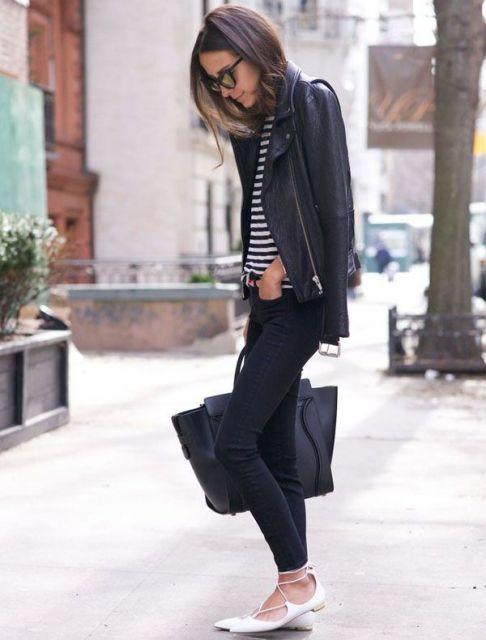 Modelo usa calça preta, blusa listrada, jaqueta preta, bolsa e sapatilha no mesmo tom.