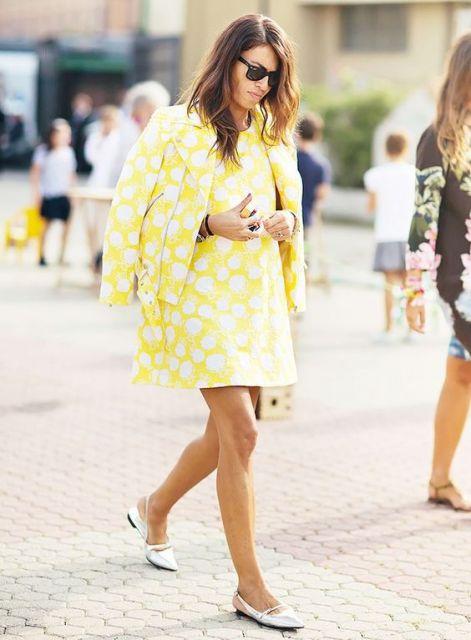 Modelo veste conjunto vestido e blaser amarelo com bolinhas brancas e sapatilha branca bico fino.
