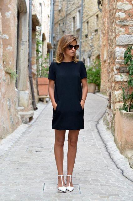 Modelo usa sapatilha de bico branca, com vestido preto de mangas modelo reo com oculos escuros.