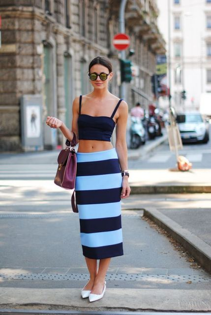 Modelo usa blusa cropped alcinha preta, saia estampa de listras e sapatilha branca com bolsa roxinha escuro.