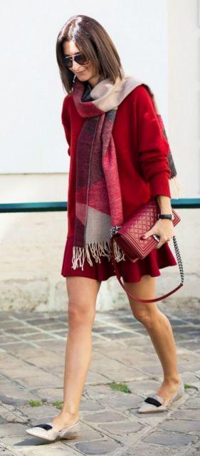 Modelo veste vestido vermelho, com cachecol estampado e bolsa vermelha de mão.
