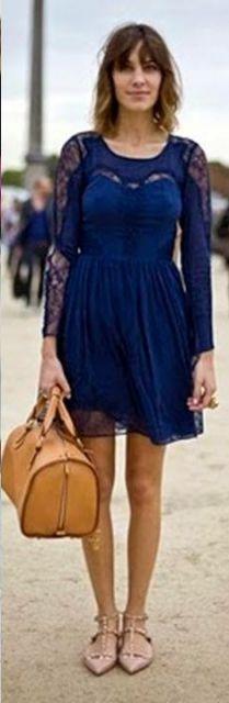 Modelo usa vestido azul royal, mangas de renda com bolsa de mao amarela de couro.