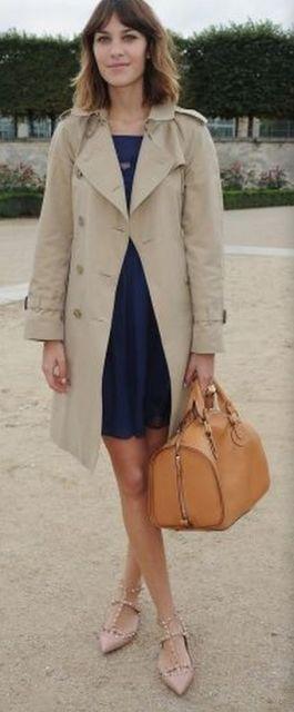 Modelo usa vestido azul, com bolsa amarela e casaco bege.