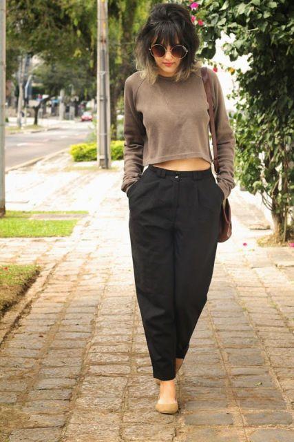 Modelo usa calça preta em alfaiataria preta, blusa larguinha manga longa e sapatilha bege..