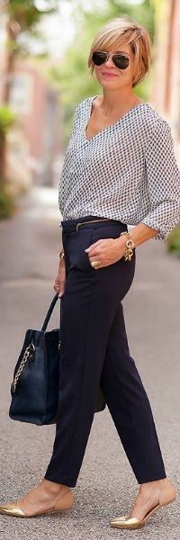 Modelo veste calça preta alfaiataria, bolsa preta, blusa cinza.