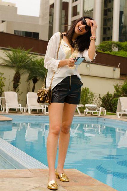 Modelo veste bermuda sintética preta, blusa branca fluída, bolsa de ombro bege e sapatilha dourada.