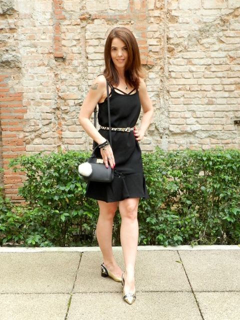 Modelo usa vestido preto acima do joelho, bolsa preta e sapatilha dourada com preto.