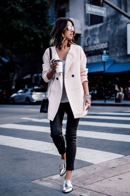 Modelo veste calça em couro preta, sapatilha no tom bolsa de ombro preta e casaco rosa longo