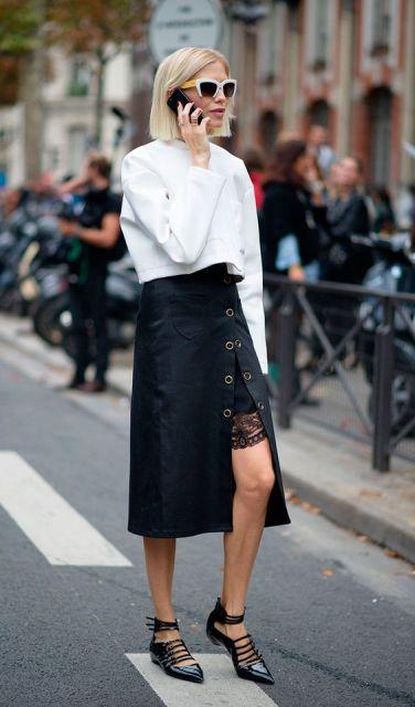 Modelo usa saia com fenda preta, blusa branca e sapatilha.