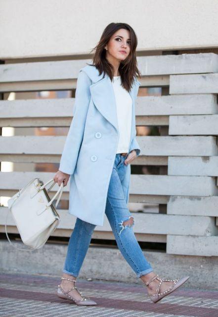 Modelo usa calça jeans azul destroyed, bolsa branca gelo, sapatilha bege com spikes, casaco azul e blusa branca.