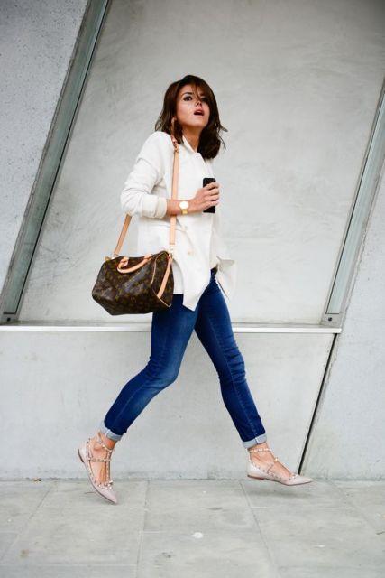 Modelo usa calça jeans azul, blusa gelo, bolsa bege e sapatilha bege com spikes.