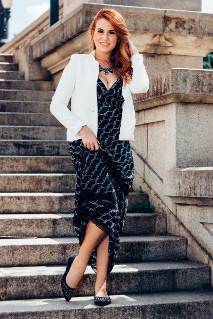 Modelo usa vestido preto em veluso, sapatilha preta e blazer branco.