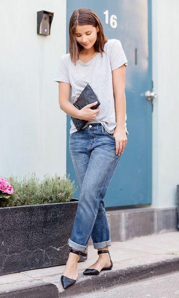 Modelo usa calça jeans, blusa cinza, caretira preta e sapatilha no mesmo tom.