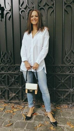 Modelo usa calça jeans, camisa branca, bolsa nude com preto e branco, sapatilha de bico preta.