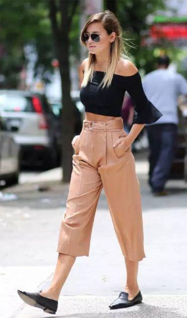 Modelo usa calça bege pantacourt, com blusa preta cropped e sapatilha preta.