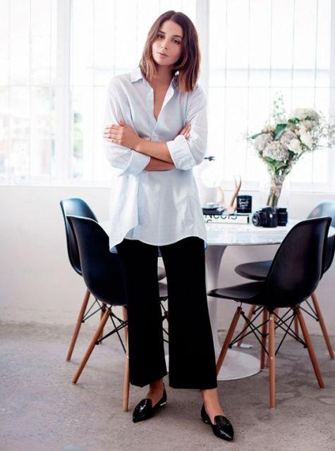 Modelo usa calça preta pantacourt, camisa azul claro e sapatilha.
