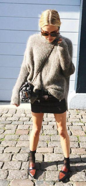 Modelo usa blusa de lã gola rolê com saia preta, meia e sapatilha marrom.