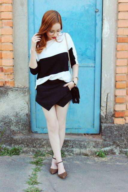 Modelo usa blusa preto e branco com saia preta e sapatilha marrom de bolinhas.