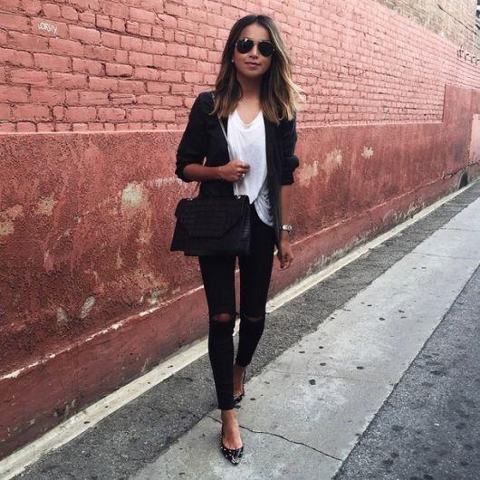 Modelo veste calça preta destroyed, blusa branca e casaco preto com bolsa no mesmo tom.