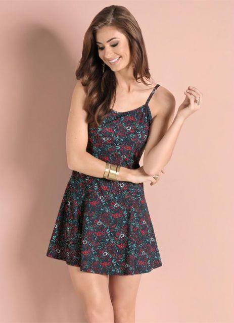 Modelo veste vestido de alcinha, na cor preta com estampa de flores miudas.