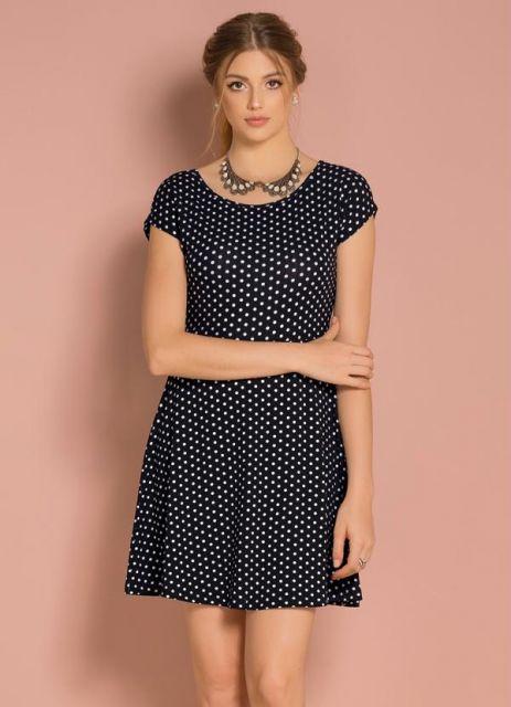 Modelo usa vestido de manguinhas mais curtas, evasê, preto com bolinhas.