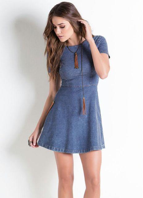 Modelo usa vestido jeans curto, azul, de manguinhas sem decote.