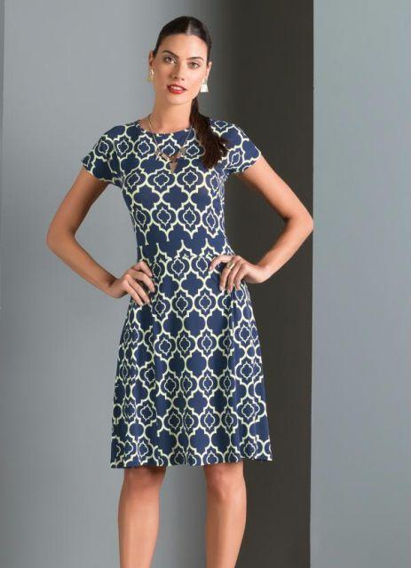 Modelo usa vestido evasê midi, estampado em tom de azul e branco.