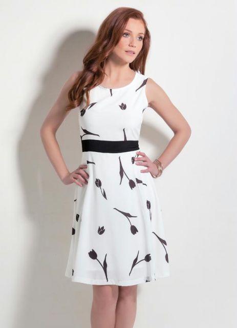 Modelo usa vestido midi evasê, branco com estampa em preto, modelgem regata, com cintinho preto.