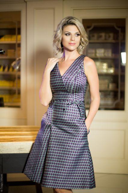 Modelo usa vestido de cetim em tons de roxo discreto, com decote.