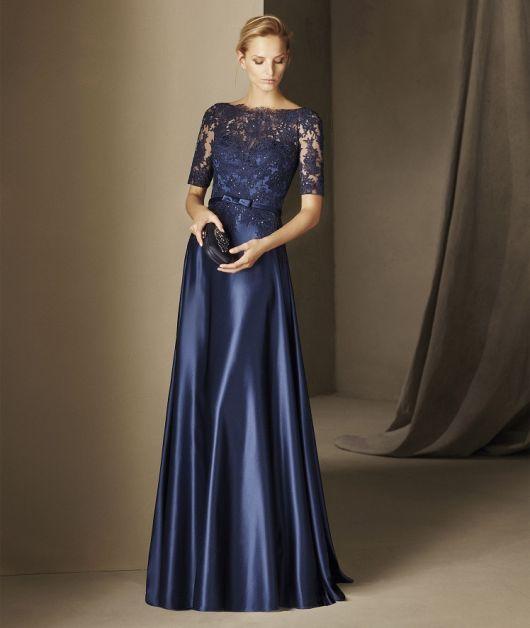 Modelo usa vestido de cetim azul marinho, com mangas e busto em renda.