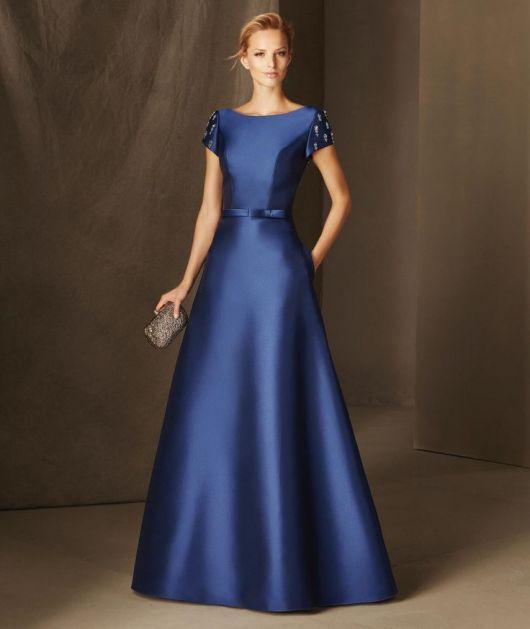 Modelo usa vestido azul marinho longo, para eventos de manguinhas curtas.