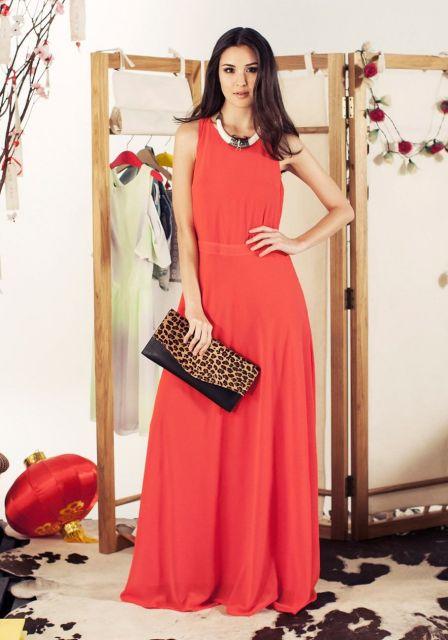 Modelo usa vestido laranja, regatinha com bola carteira de onça.