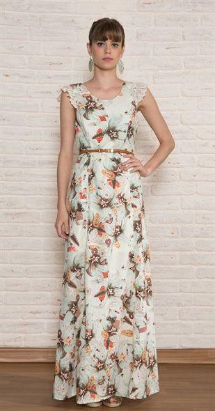 Modelo veste vestido longo evasê casual , na cor branca com estampa de flores.