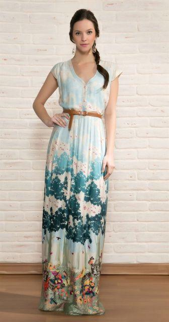 Modelo veste vestido branco com estampa azul forte e turqueza, com cintinho fino em tom terra.
