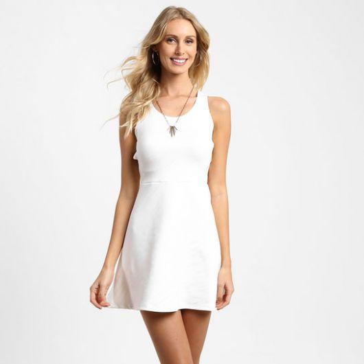 Modelo veste vestido branco, alcinhas largas, liso, com colar de pingente.