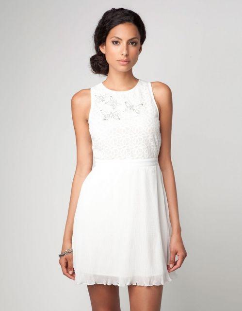 Modelo usa vestido branco com detalhes de borboletinhas bordadas no busto.