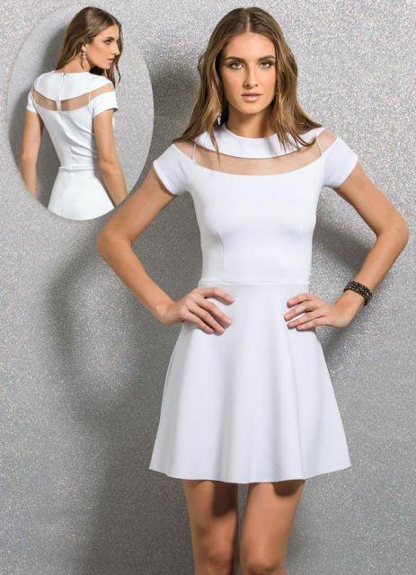 Modelo usa vestido branco, curto evasê de manguinhas, com detalhe em tule na gola.