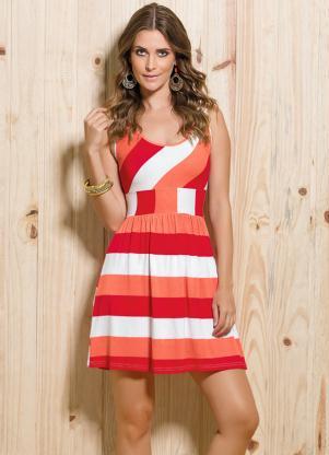 Modelo usa vestido regatinha em tons de branco, laranja e vermelho.