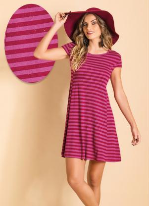 Modelo usa vestido listrado em tons de vermelho vinho e rosa.